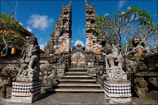 Ubud, Bali, Indonesia - 5th May 2019 : Picture of a typical Balinese temple building, with bedogol statues at the entrance of the temple gate. This temple is located in Ubud, Bali - Indonesia