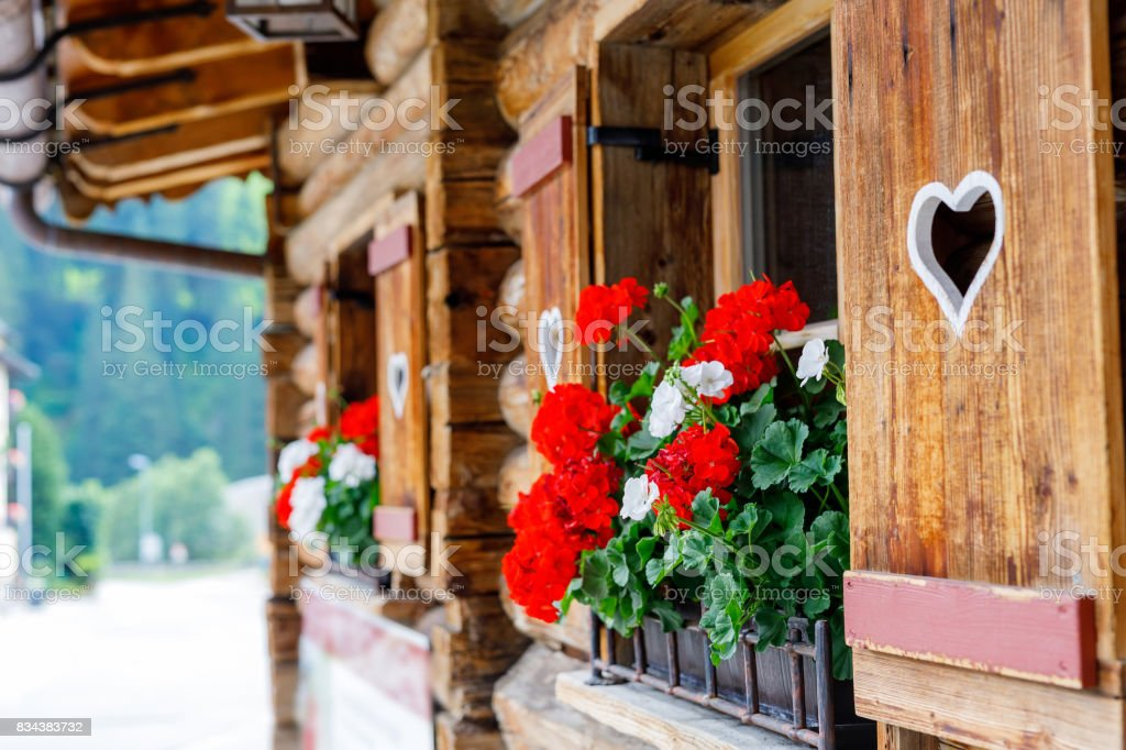 Typisch bayerische oder österreichische Holzfenster mit roten Geranien Blumen am Haus in Österreich oder Deutschland – Foto