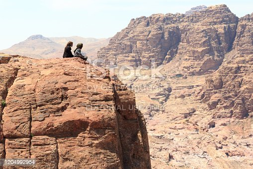 Petra, Jordan - March 28, 2019: Typical Bedouins sitting on rock at High place of sacrifice in ancient city of Petra. Bedouins are a grouping of nomadic Arab people who have historically inhabited the desert regions the Levant.