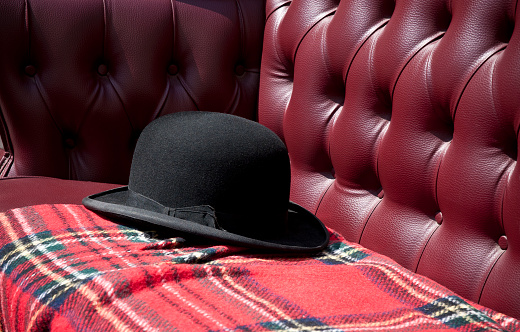 Typical black hat of a viennese cab driver (Fiaker) lies on the bench.