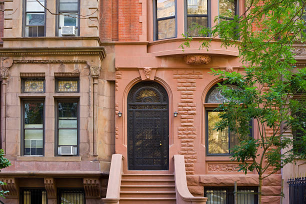 typical brownstone row house, new york city - terraced houses stock photos and pictures