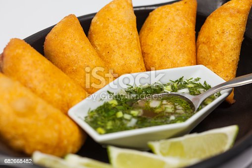 Typical Colombian empanadas served with spicy sauce on traditional black ceramic dish