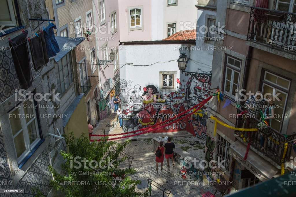 Typical Corner of Lisbon with Traditional Houses, Azulejos, Stairs, Colorful Walls and Couple of Tourists stock photo