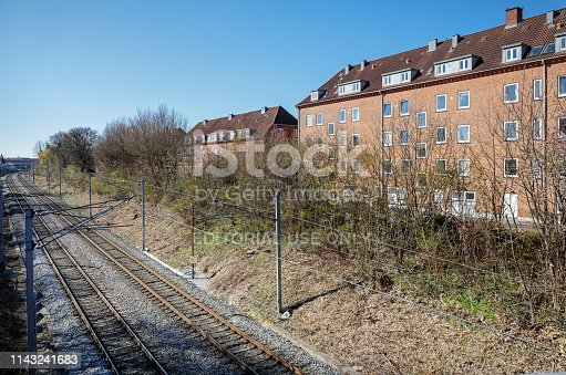 Valby, Copenhagen, Denmark - April 15, 2019: Typical house with flats close to the railroad tracks in a suburb outside Copenhagen
