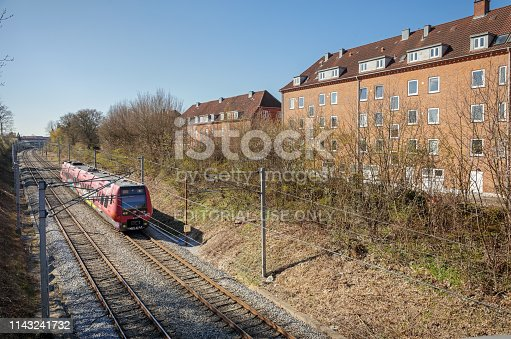 Valby, Copenhagen, Denmark - April 15, 2019: Typical house with flats close to the railroad tracks and a commuters train in a suburb outside Copenhagen