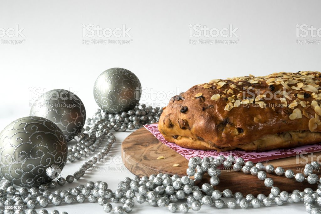 typical Dutch and German Christmas bread with almond paste, kerststol, silver holiday decorations against white background stock photo