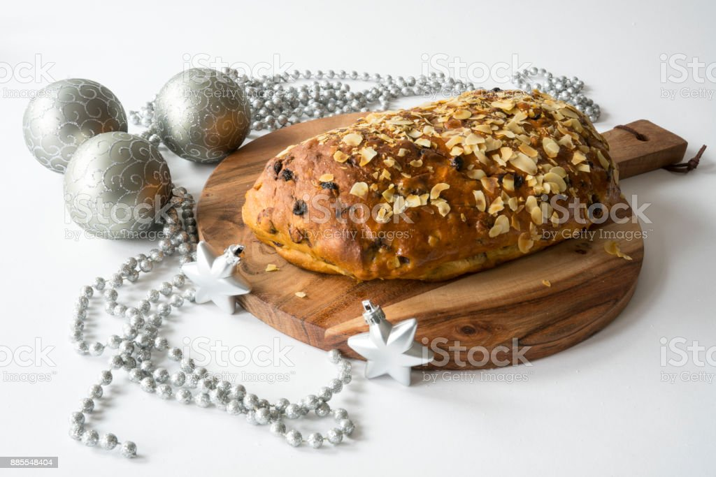 typical Dutch and German Christmas bread with almond paste, kerststol, on wooden cutting board, with silver decorations against white background stock photo