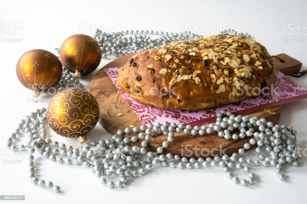 typical Dutch and German Christmas bread with almond paste, kerststol, on wooden cutting board, with golden decorations against white background stock photo
