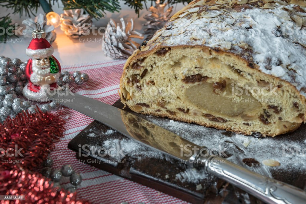 typical Dutch and German Christmas bread with almond paste, kerststol, on wooden cutting board, stock photo
