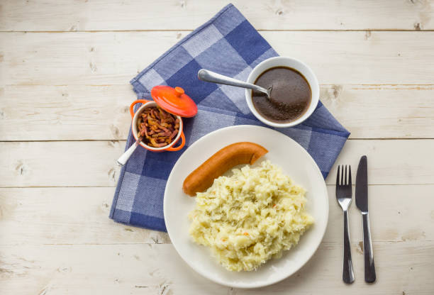 typisch nederlandse gerecht zuurkool met zuurkool, spekjes, rookworst en jus op een rustieke witte tafel - stamppot stockfoto's en -beelden
