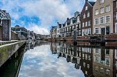 Typical dutch houses along side a canal in a dutch city under a blue and cloudy sky