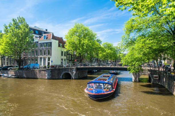 typisch nederlandse huizen en grachten in het centrum van amsterdam - rondvaartboot stockfoto's en -beelden