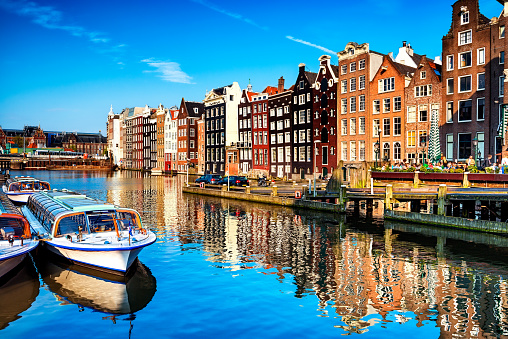 Typical canal in the center of Amsterdam. Visible are restaurants, sightseeing tourism boats at canal (gracht) waterfront and many typical dutch houses in raw and their reflection in the canal. Amsterdam, Netherlands.