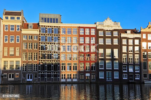 A row of typical Dutch houses built by the canal and reflected on water in Amsterdam, Netherlands