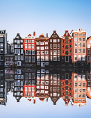 Amsterdam City Scene with many typical dutch houses in row and their reflection effect in the canal. Old 17th and 18th century brick houses along a canal in center of Amsterdam, Netherlands.