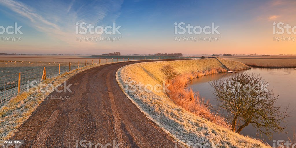 Typical Dutch landscape with a dike, in winter at sunrise stock photo