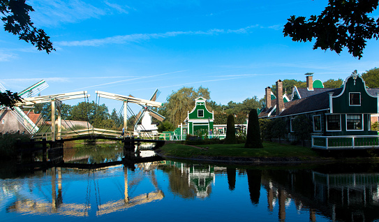 Historic dutch village with little green gable houses, windmill and drawbridge in front of a lake. Arnhem in the Netherlands. Tourism and vacations concept.