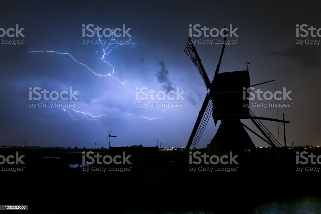 A typical dutch windmill is silhouetted against the light of a lightning bolt stock photo
