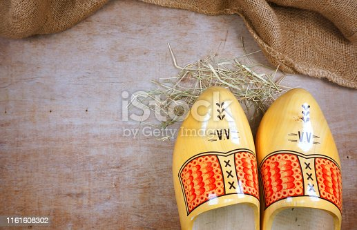istock Typical dutch wooden clogs (klompen), painted at wooden background with hessian burlap like dutch old farming and culture Amsterdam Souvenir 1161608302