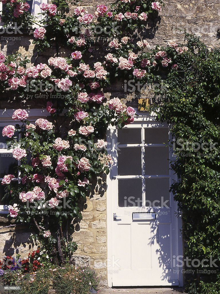 Tipica campagna inglese Cottage con rose round portiera foto stock royalty-free