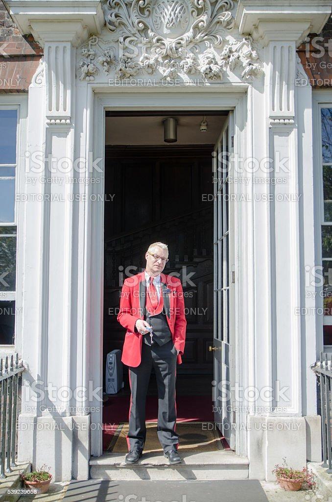 Típico inglés hombre parado en la puerta con llave foto de stock libre de derechos