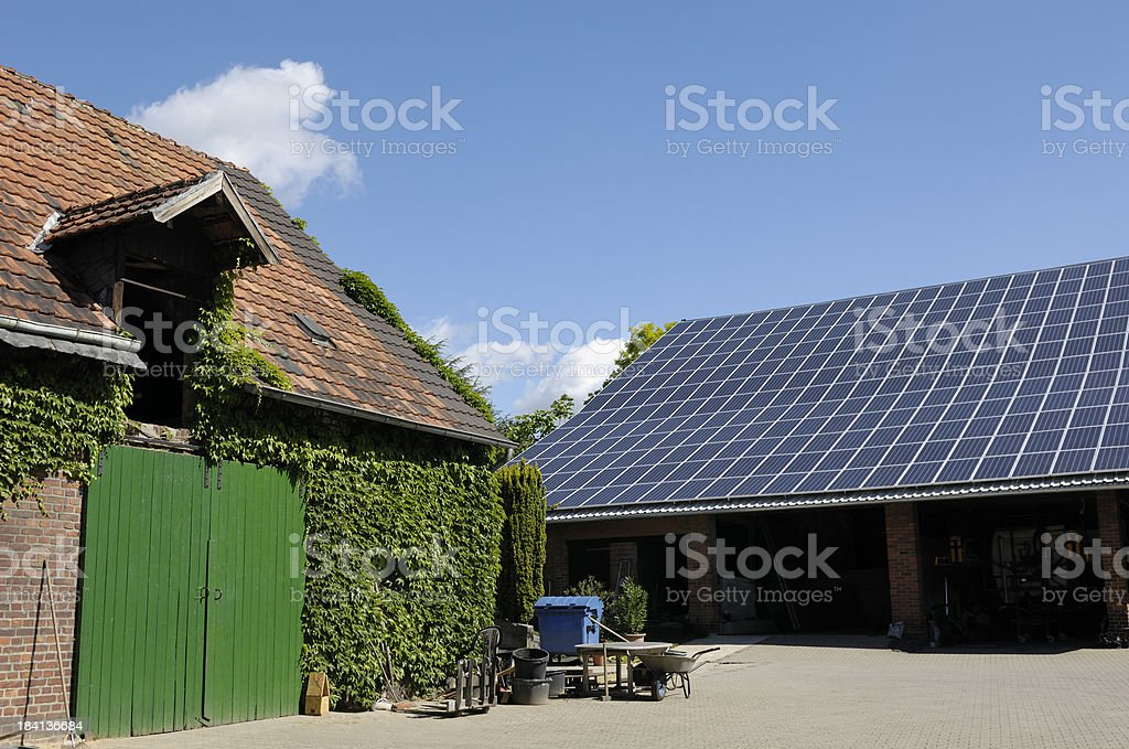 Typical farm buildings one with solar panels on the roof stock photo