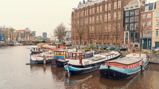 Typical floating house at Amsterdam water canal in historical center, Netherlands.