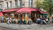Typical French cafe on the corner of two streets, Paris (France). People sit outside on the terrace, drinking and eating. A waiter serves them