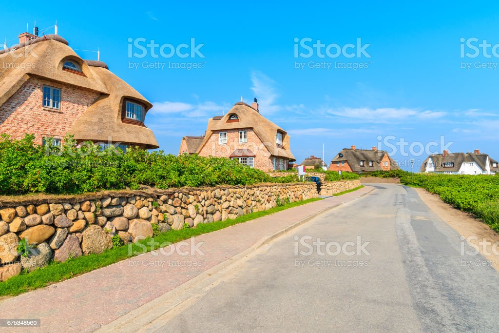 Typical Frisian red brick houses with straw roofs in Rantum village on southern coast of Sylt island, Germany stock photo