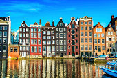 Amsterdam City Scene. Visible are many typical dutch houses in raw and their reflection in the canal. Old 17th and 18th century brick houses along a canal in center of Amsterdam, Netherlands.