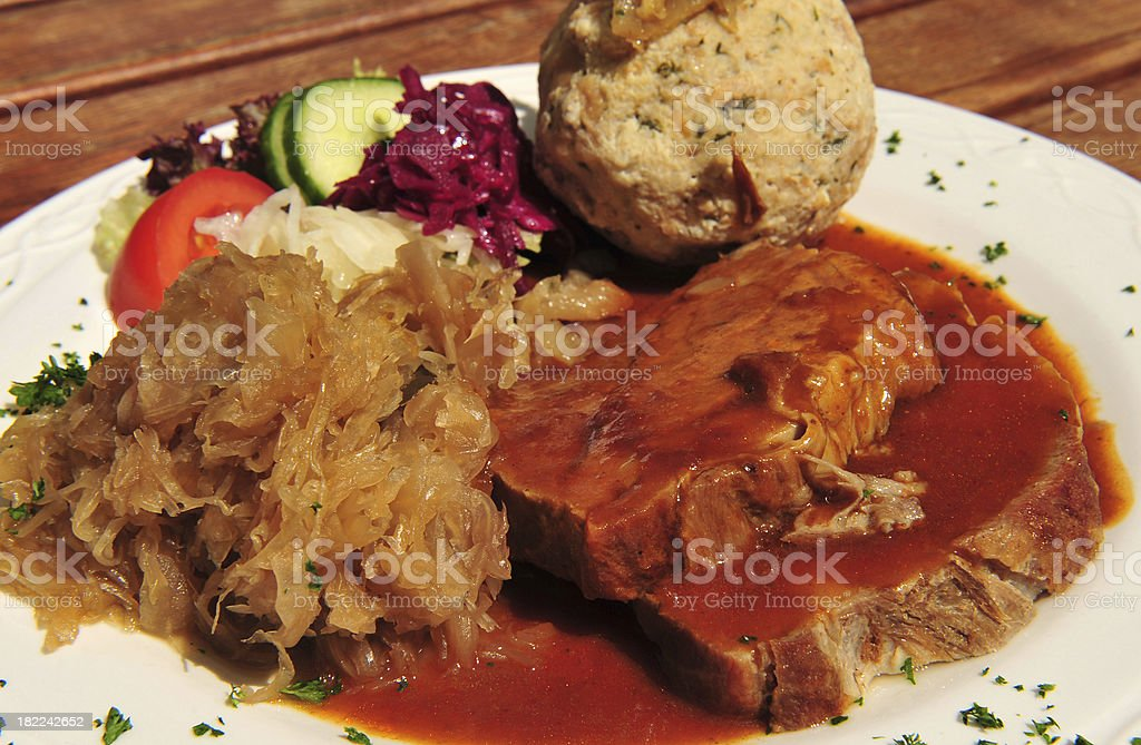 Typical German dinner of roast pork, sauerkraut, knoedel and gravy stock photo