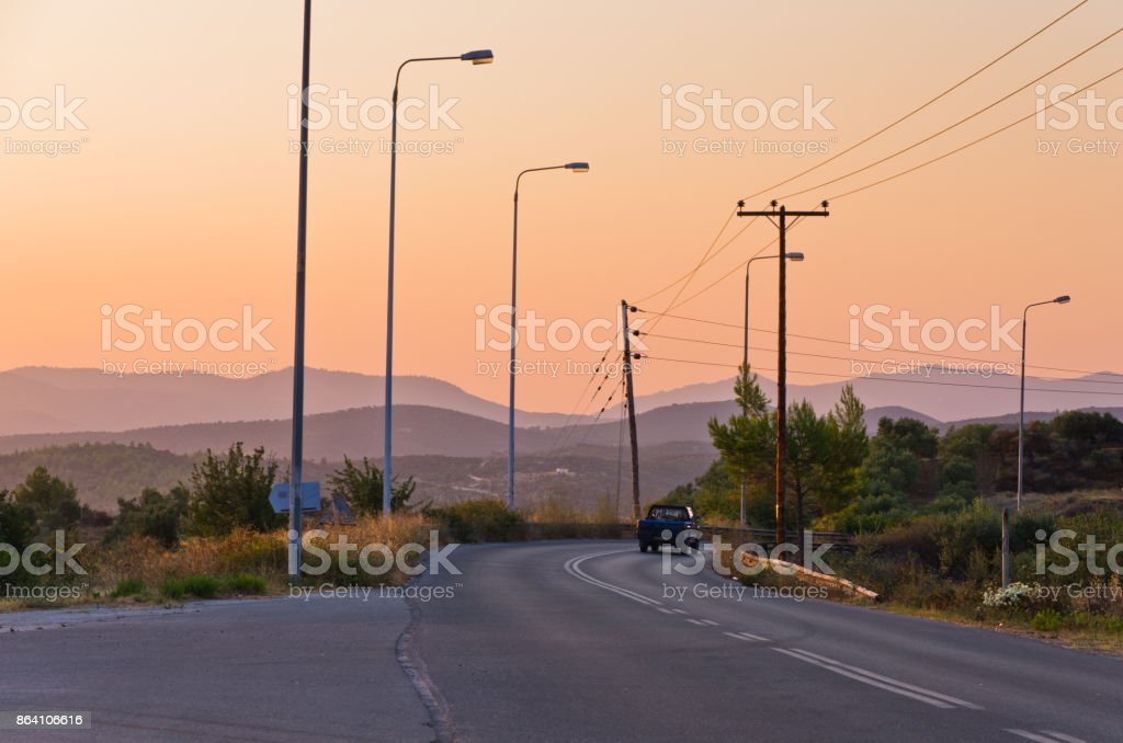 Typical greek coastal road at sunset with one pickup driving by, Sithonia royalty-free stock photo