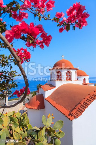 Typical Greek Monastery of Agios Savvas church with red roof, green plants and bougainvillea flowers in front and sea view in the background in Pothia, Kalymnos, Greece
