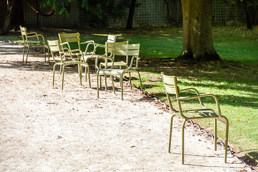 Typical green metal lawn chairs scattered alongside an alley of the Luxembourg garden in Paris, France.