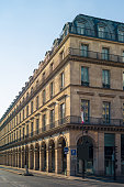 A typical Haussmann style building in Paris with balconies, arches and shops under a warm light of late afternoon.