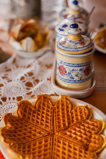 SKUDENESHAVN, NORWAY - 2016 FEBRUARY 26. Typical homemade stroopwafel of Norway, with classy porcelain settings in the background.