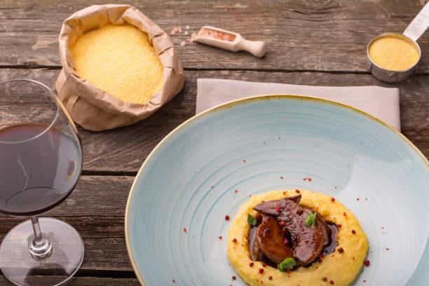전형적인 이탈리아 요리, 구운 아이 (작은 염소 고기)와 폴렌타 죽 - 폴렌타 죽 뉴스 사진 이미지