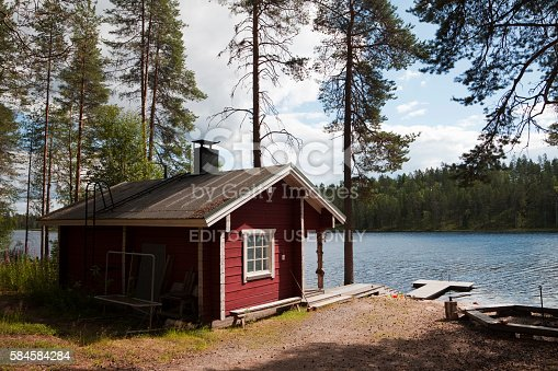 Kuhmo District, Finland - July 20, 2016: A typical sauna hut at an outdoor activity area by a lake in Finland, with a jetty and picnic area.  The sauna is an integral part of Finnish culture - there are 3 million saunas in Finland, an average of one per household, and the sauna seen as a necessity and an important part of the national identity.