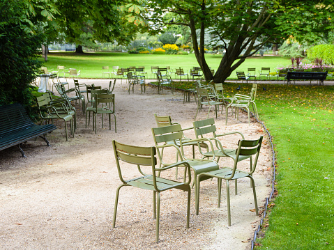 Typical metal lawn chairs of the public gardens of Paris scattered along an alley in the Luxembourg garden.