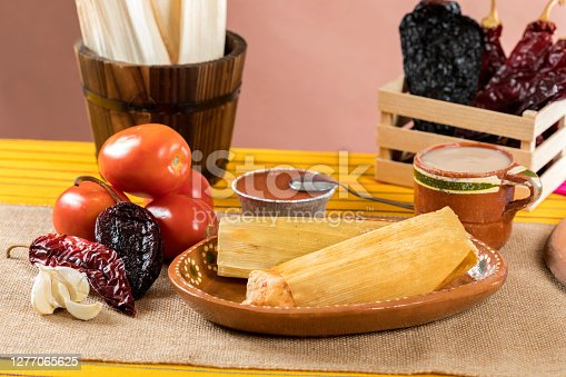 Typical Mexican food dishes with sauces on colorful table. Red mole tamales