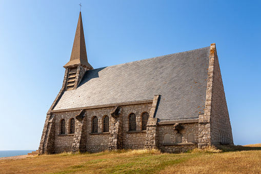 Typical Norman church: Chapelle Notre Dame de la Garde at the top of the cliff in Etretat, Normandy, France. Scenic scenery on a sunny day