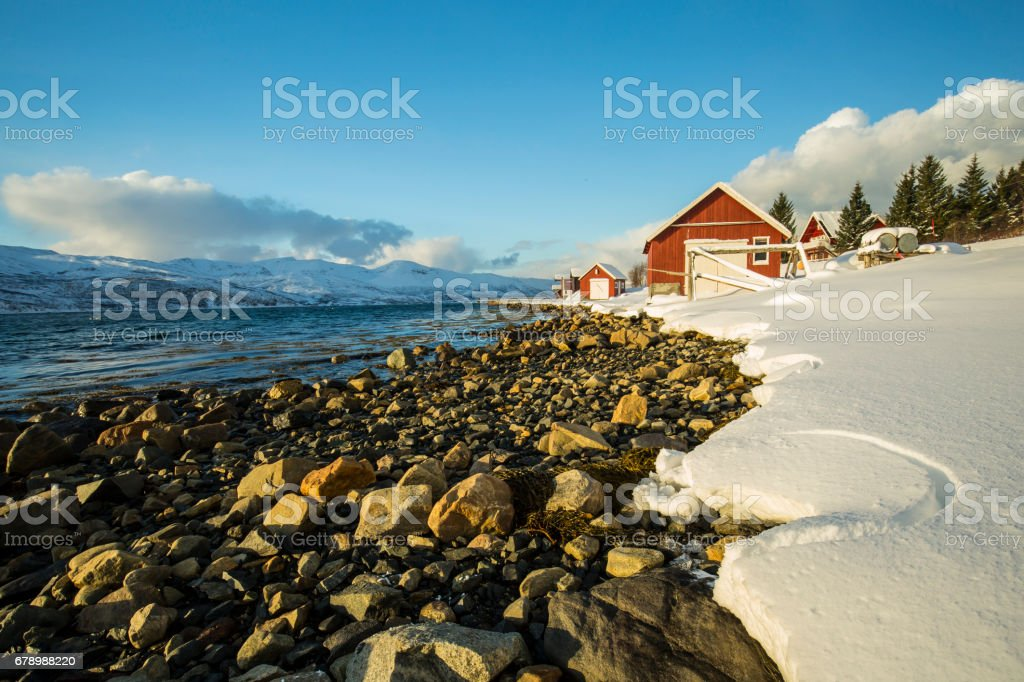 Typical norwegian warm and cozy house located at the lakeside at a fjord in a snowy winter landscape. photo libre de droits