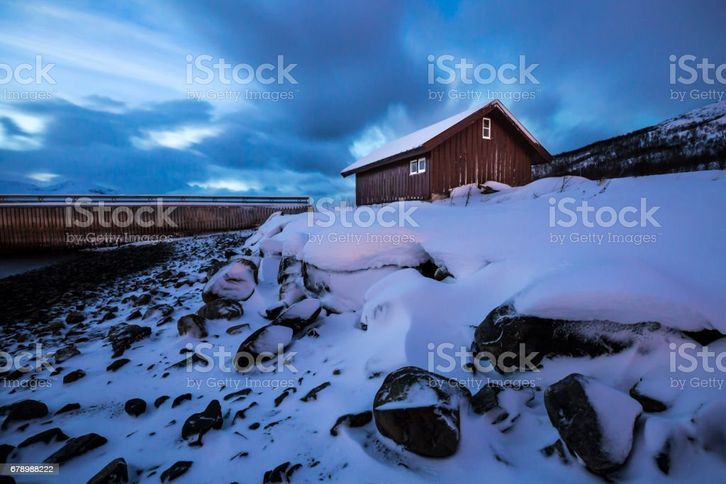 Lakeside adlı bir fiyort karlı kış manzara içinde dusk sırasında bulunan tipik Norveç sıcak ve rahat ev. royalty-free stock photo