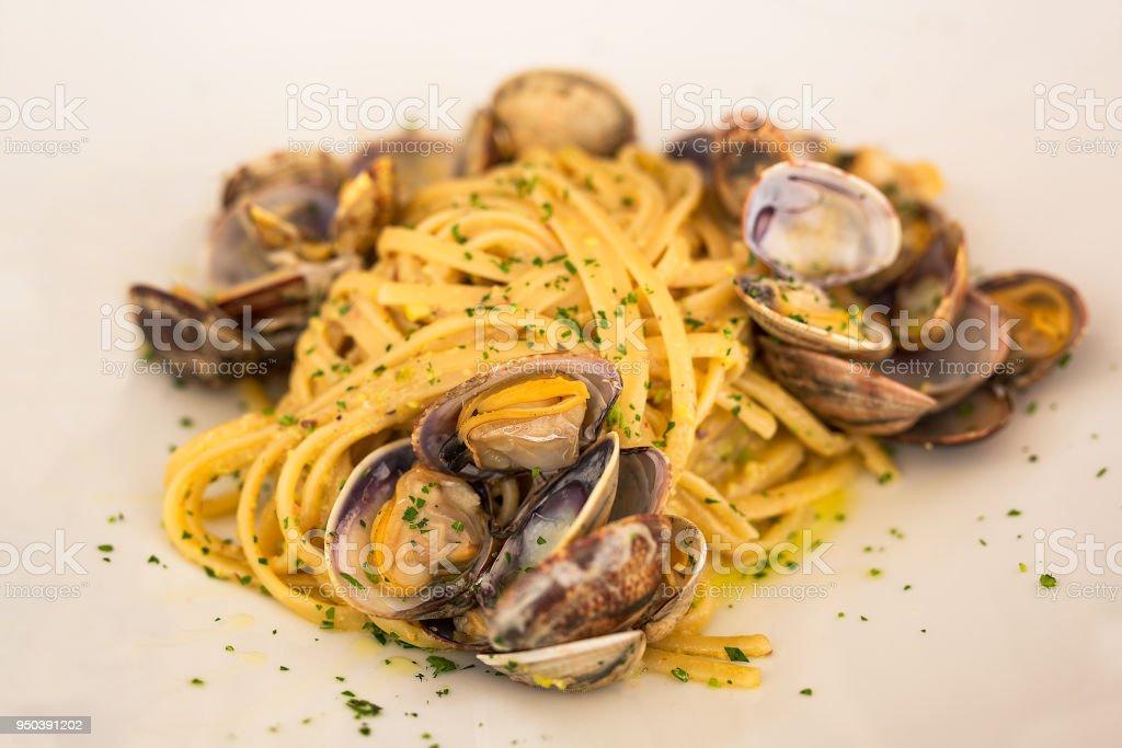 Un plato típico con pescado y marisco de la tradición italiana junto al mar - foto de stock