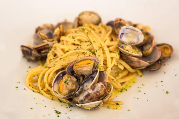en typisk tallrik med fisk och skaldjur från den italienska kuststaden traditionen - pasta vongole bildbanksfoton och bilder