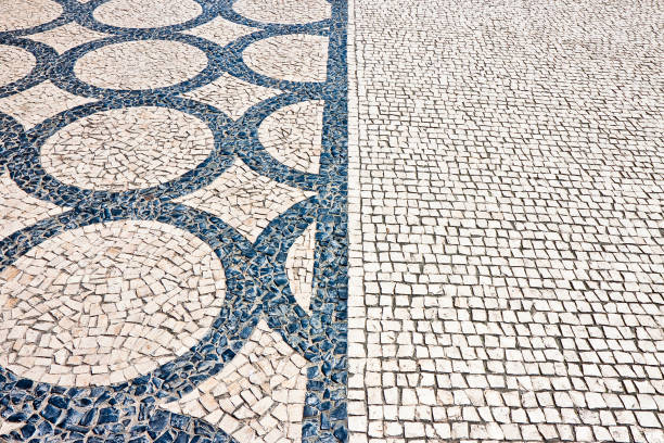 Typical portuguese floor made of small pieces of black and white stone in shape of circles and arcs (Portugal - Europe) stock photo