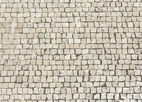 Mosaic pavers of small stones. Abstract background of old cobblestone pavement close-up.