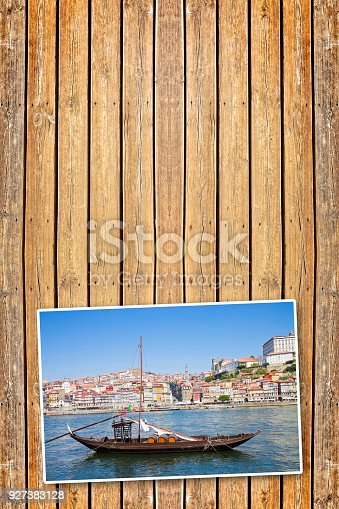 Typical portuguese wooden boats, called -barcos rabelos-, used in the past to transport the famous port wine (Porto - Oporto - Portugal - Europe) - Concept image with copy space on wooden background