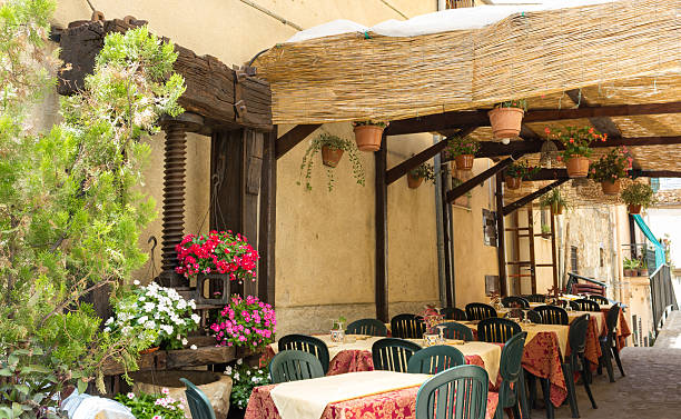 typical restaurant typical summer restaurant with outdoor courtyard for intimate romantic encounters inn stock pictures, royalty-free photos & images