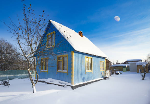 Moscow Region, Russia - January 6, 2017: Typical Russian dacha in winter. Blue wooden house, tree, snow all around and Moon in the sky Painted cabin in snowy landscape russian dacha stock pictures, royalty-free photos & images